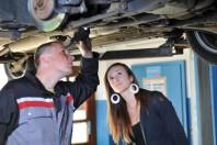Ein Mechaniker und eine junge Frau betrachten ein Auto von unten
