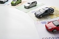Kleine Spielzeugautos stehen auf unterschiedlichen Geldscheinen