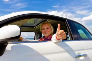 Junge Frau freut sich über ihr Auto